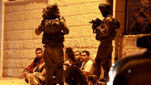 Israeli security forces detain Palestinian men in the West Bank village of Beit Sahur