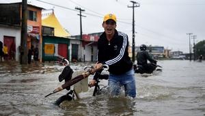 A cyclist pushes his bike through a waterlogged avenue in Recife, Brazil
