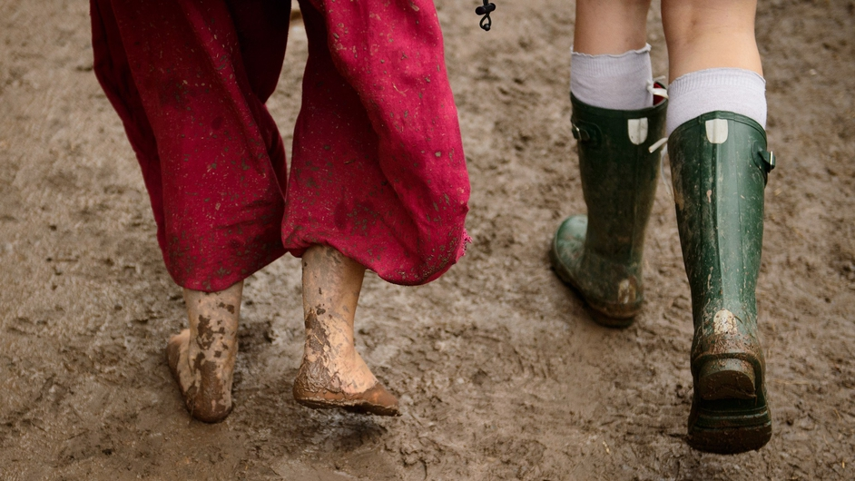 A festival-goer wades barefoot through muck at Glastonbury 2014
