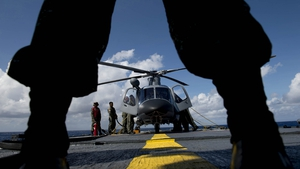 Philippine Navy personnel stand in front of a helicopter before it takes off during a bilateral maritime exercise between the Philippine Navy and the US Navy