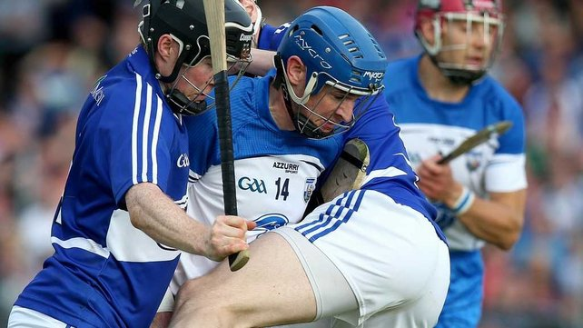 Shane Walsh is tackled by two Laois players