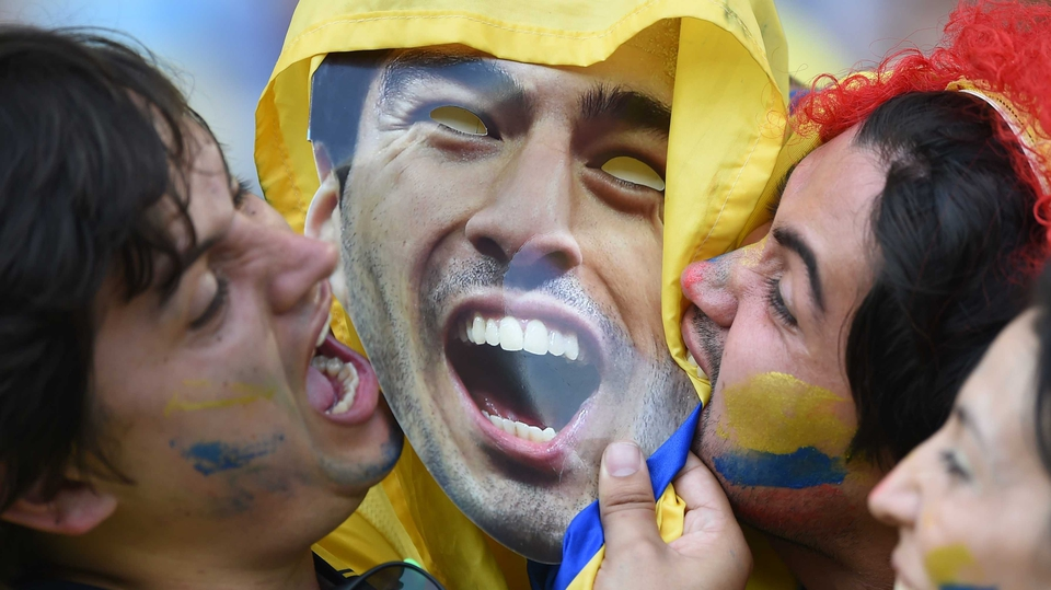 Colombia fans bite an image of Luis Suarez
