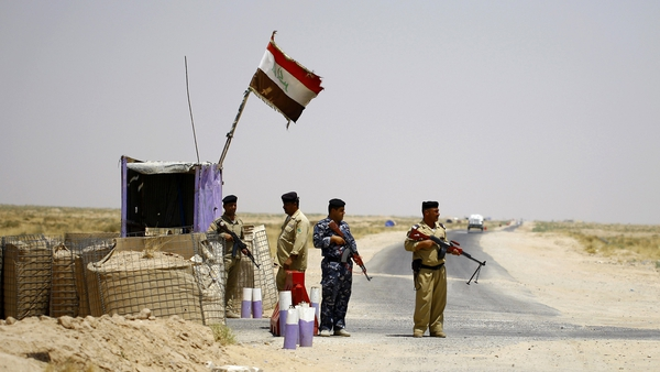 Shia fighters secure an area west of the central holy city of Najaf on a road leading to Anbar