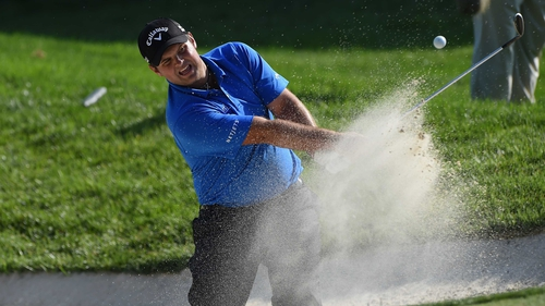 Patrick Reed hits out of a bunker on the 17th hole during the third round of the Quicken Loans National
