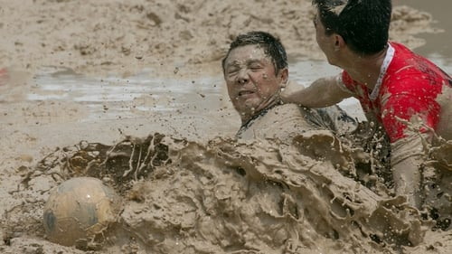Players go for the ball in mud during a match of Swamp Soccer at the Yuetan Sports Center in Beijing, China