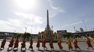 Thai Buddhist monks walk along a road to receive alms from the public during a merit making ceremony at the Victory Monument in Bangkok