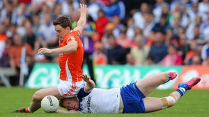Armagh's Charlie Vernon takes a seat as he and Kieran Hughes of Monaghan go for the ball