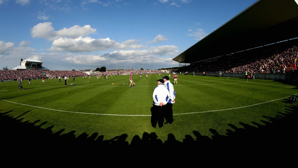 Two umpires watch the Galway team warm up ahead of their Leinster SHC semi-final against Kilkenny