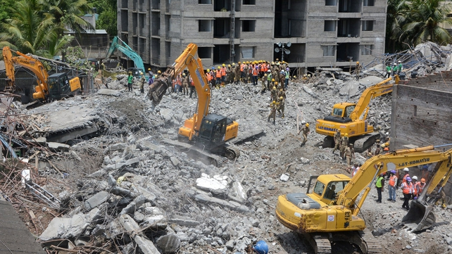 Rescue workers clear rubble at the site