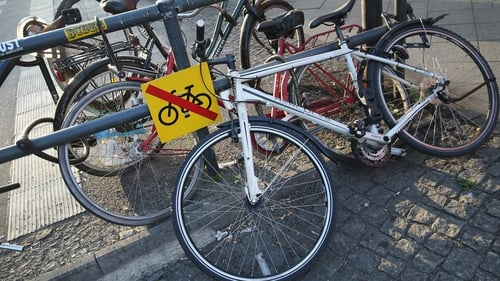Bicycles lie chained to a barrier next to a sign explicity forbidding their presence at Alexanderplatz