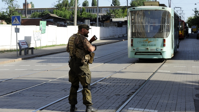 A pro-Russian militant stops tram traffic in the centre of the eastern Ukrainian city of Donetsk