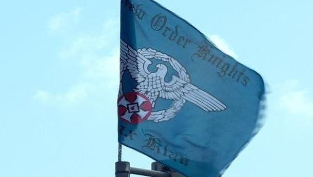 The flag features an Aryan eagle and red KKK symbol and bears the words New Order Knights and Ku Klux Klan
