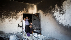 Relatives and neighbours of a suspect in the killing of Israeli teenagers in the West Bank, Amer Abu-Aisheh, stand in a house destroyed by the Israeli army in response to the killings