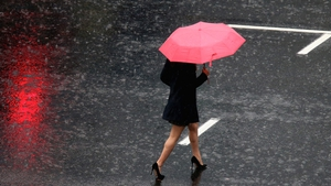 A pedestrian crosses in the intersection of Queen Street and Victoria Street during heavy rain in Auckland, New Zealand