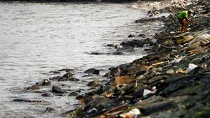 A Filipino walks among plastic garbage at the shore of Manila Bay, Philippines