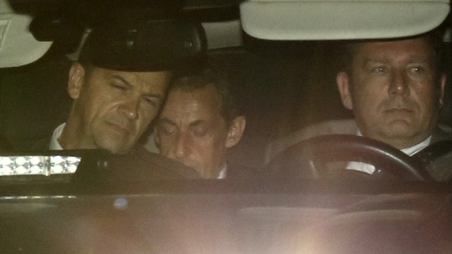 Nicolas Sarkozy (c) leaves the Financial Investigation Unit in Paris early today