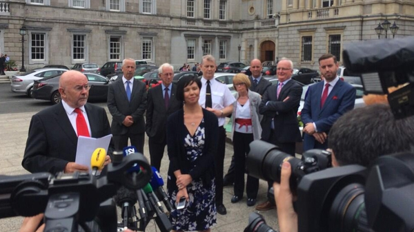 Ruairi Quinn made the announcement outside Leinster House at midday
