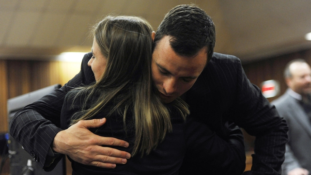 The South African athlete hugs a supporter in court