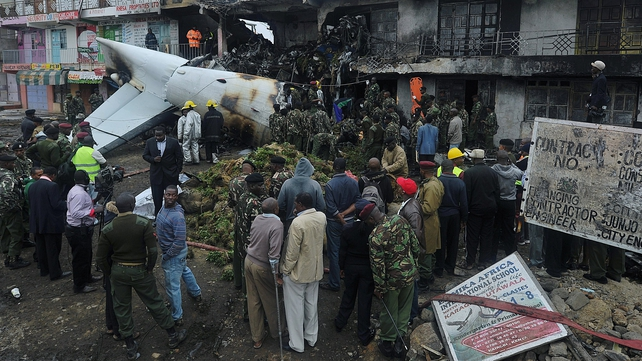 People look on at the plane, which crashed into a commercial building