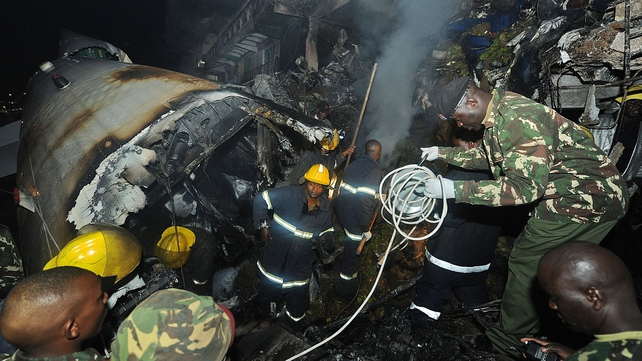 Police search the wreckage of the crashed plane