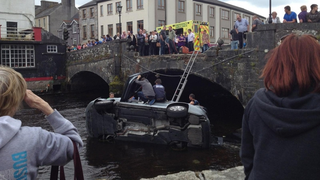 The car smashed through a concrete wall and ended on its side in shallow water