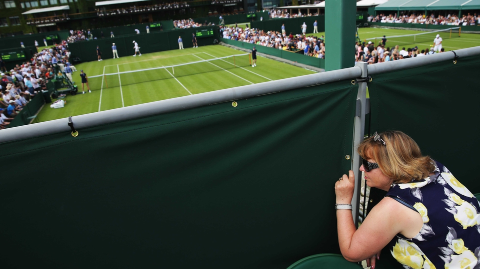 A fan peaks through a gap in the fence to watch the action at Wimbledon