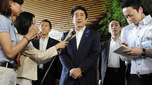 Japanese Prime Minister Shinzo Abe (C) speaks to reporters at his official residence in Tokyo