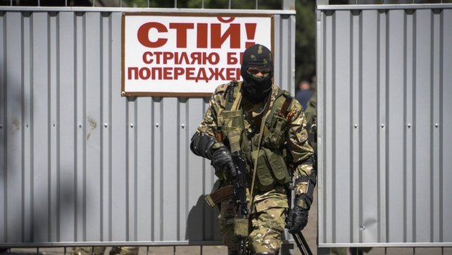 A Pro-Russian rebel on watch at the gate of the seized National Guard military base in Donetsk