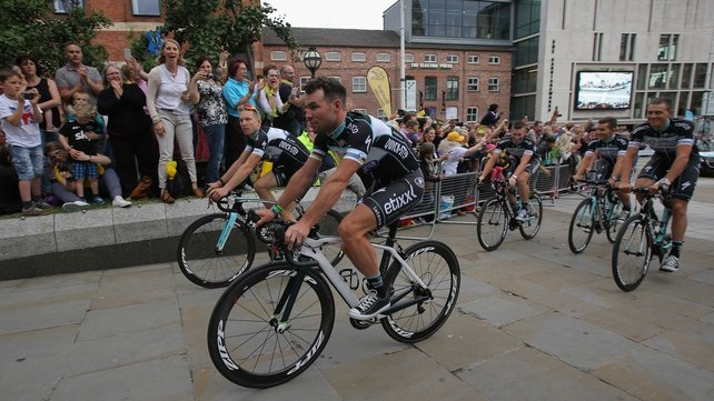 Mark Cavendish and his team-mates are greeted by supporters as they ride through Millennium Square in Leeds ahead of the start of the Tour