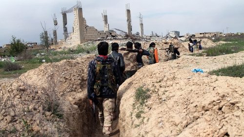 Rebel fighters carry their weapons as they walk along a trench in the northeastern city of Deir Ezzor
