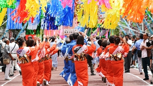Dancers dressed in traditional costume perform dance under the colorful ornaments of Tanabata during the Shonan Hiratsuka Tanabata Festival in Japan