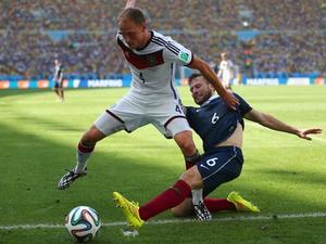Yohan Cabaye (R) tackles Germany's Benedikt Hoewedes