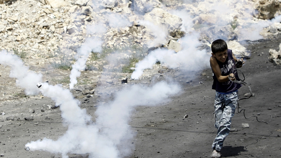 Tear gas canisters land near a Palestinian boy during clashes over expropriation in the village of Kfar Qaddum