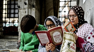 A woman with her children read the Holy Koran and attend the Friday prayers at Eyup mosque in Istanbul