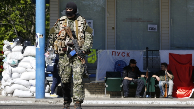 A pro-Russian armed man guards a check point outside Slaviansk earlier this month