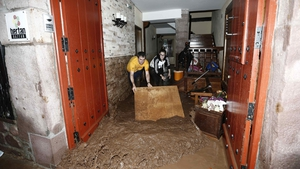 Residents scrape mud from their flooded house after flooding in Pamplona, northern Spain