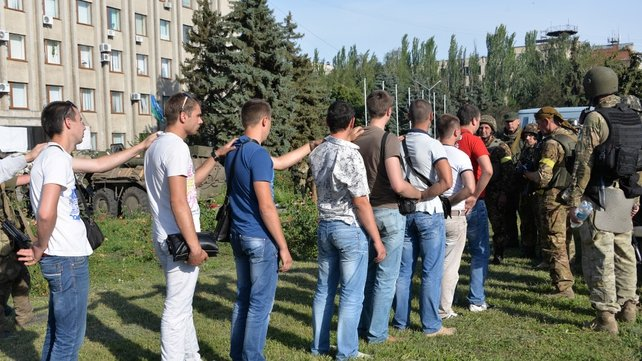 Ukrainian soldiers check identity documents of local men