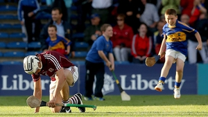 Galway's Daithi Burke slumps to the ground dejected while a young Tipperary fan is elated after the match