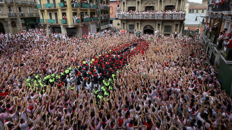 Revellers wave as the band plays at the Festival of the San Fermin Running of the Bulls