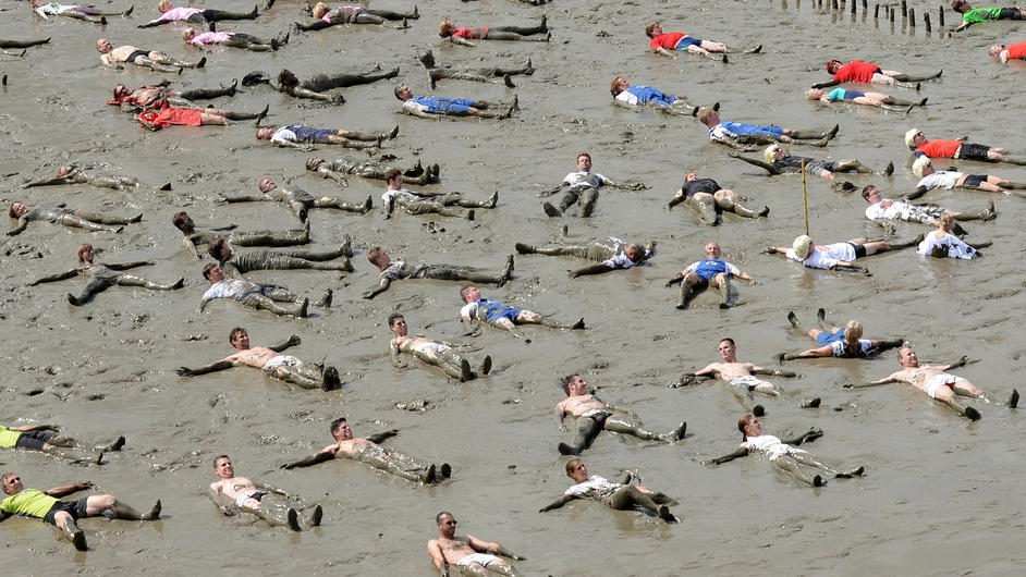 Participants lie in mudflats outside Brunsbuettel during a record attempt event as part of the Mudflat Olympics