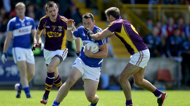 Laois' John O'Loughlin tries to avoid the presence of Brian Malone