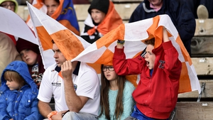 Armagh fans cover themselves from the rain in Clones
