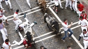 Two 'mozos' or runners fall during the first bull run of the 2014 Sanfermines in Pamplona, Spain
