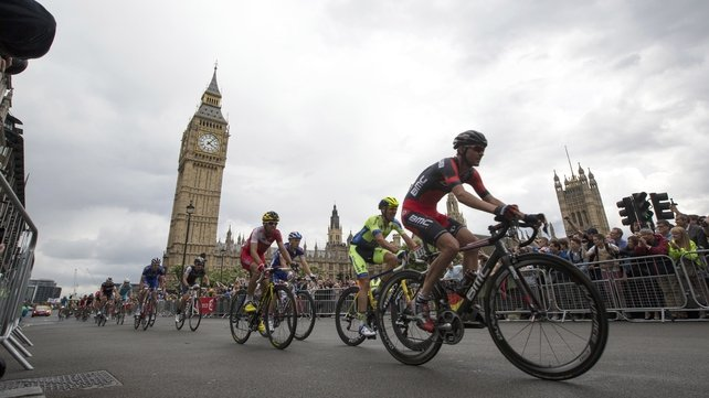 Crowds cheer as cyclists competing in the Tour de France pass through London's Parliament Square
