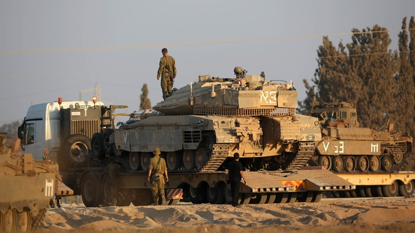 An Israeli Merkava tank takes position at the border with Gaza