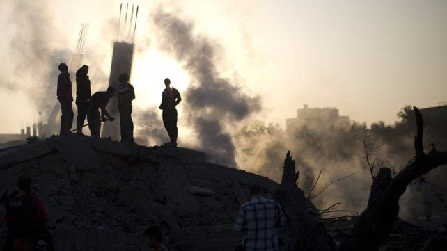 Palestinian men examine the site of one of the air strikes