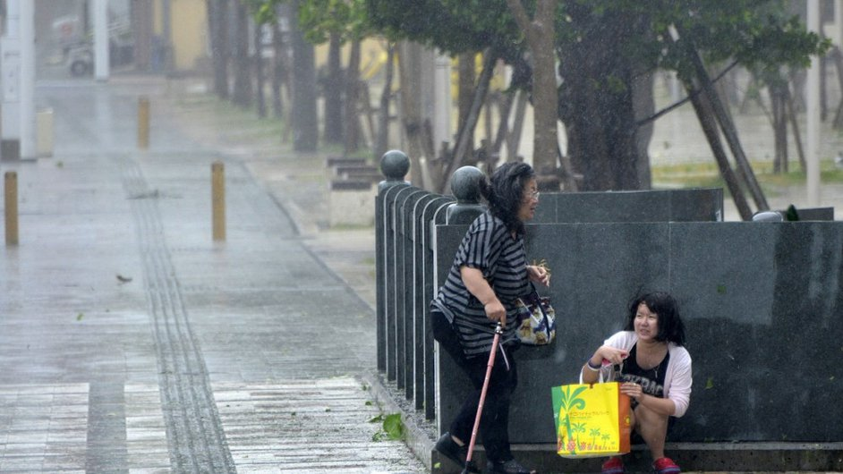 Two women seek shelter from strong winds hitting the city of Naha on Okinawa