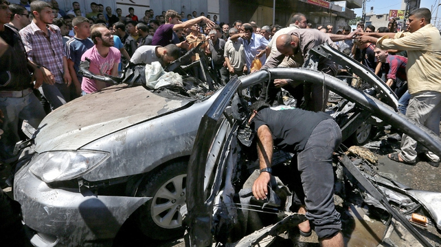 Palestinians inspect a destroyed car belonging to militants following an Israeli airstrike in Gaza City