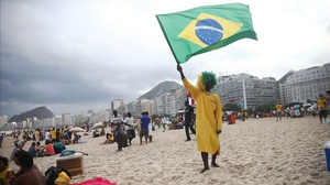 A Brazil fan held his country's flag at the Copacabana in Rio ahead of the match