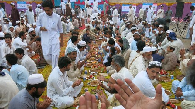 Internally displaced Pakistani civilians pray before breaking their fast during Ramadan